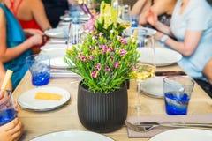 Dinning mit Familie, Freunde Verwischte keine Gesichtsleute, die Mahlzeit beim Sitzen am dinning Tisch mit Fokus auf dem Blumento stockfoto