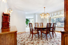 Dinning room with floral patterned rug, deep toned wood and chan Stock Photo