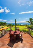 Dinning table on patio deck with large view and lawn. Outdoor dinning table on patio deck with large ocean view and lawn royalty free stock photos