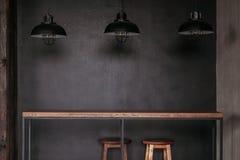 Dinningslijst in de eetkamer van de zolderstijl met zwarte lampen wordt geplaatst die Stock Foto
