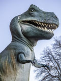 Dino. Representation in large scale of the huge and ferocious Tyrannosaurus Rex, T-Rex, against the blue sky with some vegetation Royalty Free Stock Photos