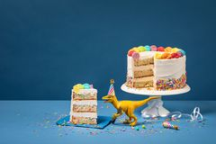 Dinosaur toy and Colourful Birthday Cake. Hungry toy dinosaur wearing a hat and holding a fork next to a birthday Cake on a Blue background stock image