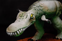 Dinosaur Cake. Close up of a handmade dinosaur cake with big teeth on a black background Stock Photo