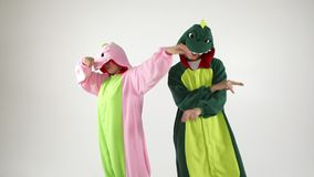 Dinosaur costumes absurd dancing couple. Funny party mood. White background video footage. Dinosaur costumes fun absurd dancing couple. Funny party mood. White stock video footage