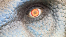 Dinosaur Eye. A close up view of a flaming and angry eye of a dinosaur Royalty Free Stock Images