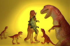 Dinosaur Family Dinner. A family of plastic T-rex dinosaurs gather together for a meal of Stegosaurus Royalty Free Stock Photo
