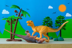 Dinosaur fight scene on wild models background. Closeup Stock Photos