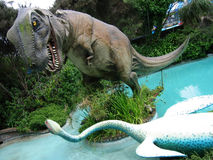Dinosaur figures fighting. Close up of replica figure of Tyrannosaurus Rex dinosaur fighting long necked aquatic creature in water, amusement park scene stock photo