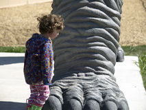Dinosaur foot. This little girl is checking out the foot on a brontosaurus ,probably thinking what a pedicure job Royalty Free Stock Photo