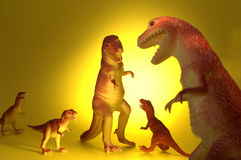 Dinosaur Gathering. A family of plastic toy T-rex dinosaurs gather Stock Image