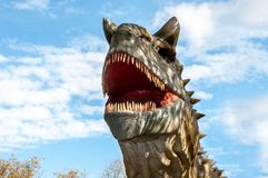 Dinosaur Karnotavr. Huge full-size head. On a background of blue sky with clouds royalty free stock image