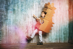 Dinosaur. Little dreamer boy playing with a cardboard dragon, dinosaur. Childhood. Fantasy, imagination Stock Images
