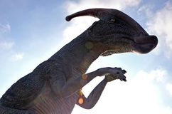 Dinosaur Parasaurolophus against blue sky with clouds stock photo