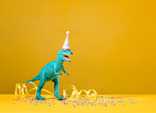 Dinosaur Party. Toy dinosaur with party hat on a yellow background royalty free stock photo