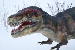 Dinosaur in snow. Dinosaur in winter on the white snow with cloudy sky Stock Photography