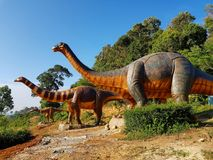 The dinosaur statues are in the park stock photos