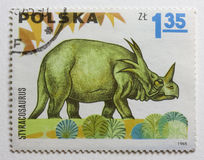Dinosaur (styracosaurus) on vintage post stamp Royalty Free Stock Photography