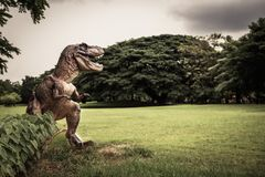 Dinosaur , T-rex with tree branches against on the nature.  Stock Image