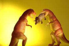 Dinosaur Take Over. Two plastic toy T-Rex dinosaurs and a Triceritops meal Royalty Free Stock Images