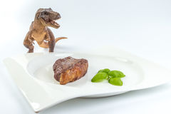 Dinosaur Tyrannosaurus Rex looking at a slice of barbecued cow b Royalty Free Stock Images