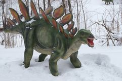 Dinosaur in snow. Dinosaur in winter on the white snow with cloudy sky Royalty Free Stock Images