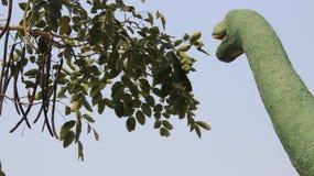 Dinosauriestaty med sidor och fröskidor royaltyfri foto