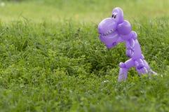 Dinosaurio animal del globo púrpura en la hierba verde del patio trasero Imagen de archivo
