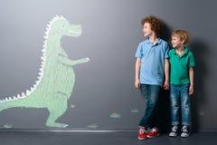 Dinosaurio lindo y dos muchachos fotografía de archivo libre de regalías