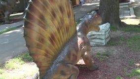 Dinosaurio realista de Dimetrodon en parque detrás de la parte posterior metrajes