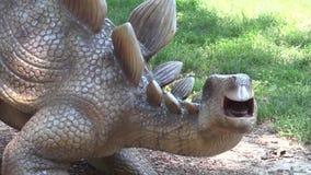 Dinosaurio realista del Stegosaurus en cabeza y cuello del parque con la espina almacen de metraje de vídeo
