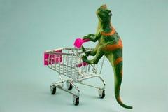 Dinosaurio verde plástico con el carro de la compra imagen de archivo