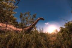 Dinosauro in erba alta ad alba Fotografie Stock Libere da Diritti