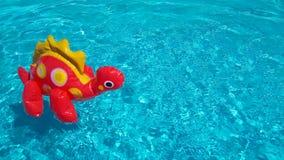 Dinosauro gonfiabile in acqua d'increspatura pulita dello stagno Concetto di vendita di vacanze estive Un giocattolo dei bambini  fotografia stock libera da diritti