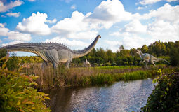 Dinosaurs Park in Leba Poland. Touristic attraction in northern Poland, Dinosaurs Park in Leba. Two big animal statues seen across a pond Royalty Free Stock Image