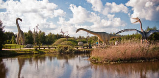 Dinosaurs Park in Leba Poland. Touristic attraction in northern Poland, Dinosaurs Park in Leba. Two big animal statues seen across a pond Royalty Free Stock Images
