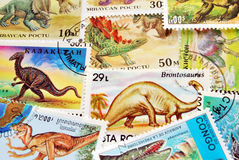 Dinosaurs postage stamps background. Close up of dinosaurs stamps horizontal background Royalty Free Stock Photos
