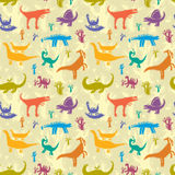 Dinosaurs. Seamless pattern with colorful dinosaurs on a background of ancient trees Stock Photos