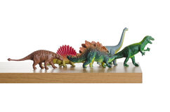 Dinosaurs walking off a ledge. Dinosaurs figurines placed together on a ledge Royalty Free Stock Image