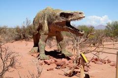 Dinosaurusmodel in het zand stock foto's