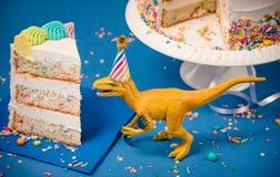 Dinossauro e fatia de bolo de aniversário imagem de stock