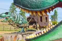 Dinossauros na atração 1912 da borda da estrada da reminiscência do celeiro do log imagem de stock