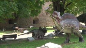 Dinossauros realísticos no parque de Dino em torno do banco para sentar-se vídeos de arquivo