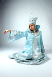 DINOTOPIA. Girl dressed as Snow Queen sits on a blue background outstretched hand Stock Photography