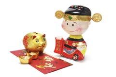Dios de la prosperidad y de Piggybank de oro chino Imagen de archivo