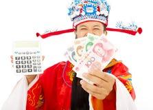 Dios de la riqueza que lleva a cabo una máquina del cálculo y una moneda china Imagen de archivo libre de regalías