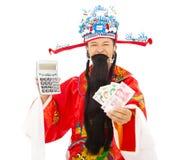 Dios de la riqueza que lleva a cabo una máquina del cálculo y una moneda china Imagenes de archivo
