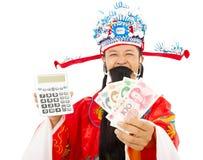 Dios de la riqueza que lleva a cabo una máquina del cálculo y una moneda china Imagen de archivo