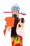 Dios de la riqueza que sostiene el sobre rojo y el teléfono móvil Imágenes de archivo libres de regalías