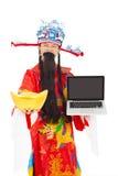 Dios de la riqueza que sostiene un lingote del ordenador portátil y del oro Fotografía de archivo