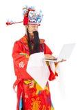 Dios de la riqueza que sostiene un ordenador portátil Imagen de archivo libre de regalías